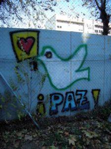 """Foto vrededuif op betonnen muur met in het Spaans """"Paz"""""""