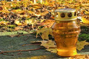 Licthje in goudkleurige houder met op de achtegrond afgevallen gele bladeren